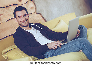 Loving his new laptop. Cheerful young man using his laptop and looking at camera with smile while sitting on couch at home