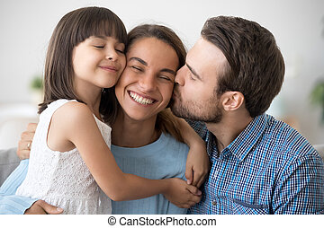 Loving husband and cute kid daughter embracing kissing happy wom