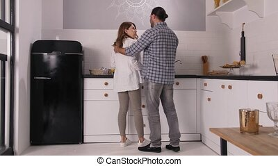 Attractive joyful couple expecting baby cuddling and chatting in home kitchen. Caring man kissing, hugging and stroking beloved pregnant wife standing at kitchen while making breakfast