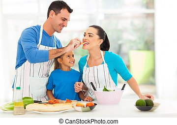 loving husband feeding wife a piece of tomato while cooking