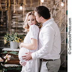 Loving husband gently hugging his pregnant wife