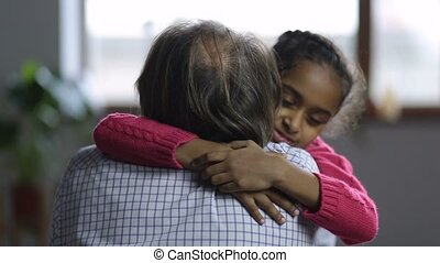 Loving little girl embracing her grandfather - Adorable...