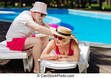 Caring loving retired man making massage for his modern wife...