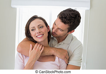 Loving man embracing woman from behind