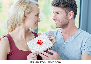 Loving man giving his wife a gift