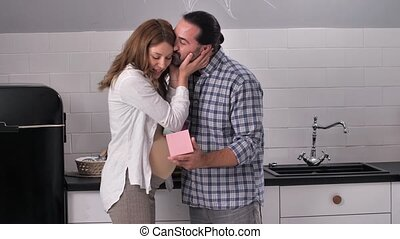Close-up of attentive husband giving present to joyful pregnant woman and kissing her gently. Happy pregnant couple communicating in kitchen, surprised female hugging beloved man for nice gift