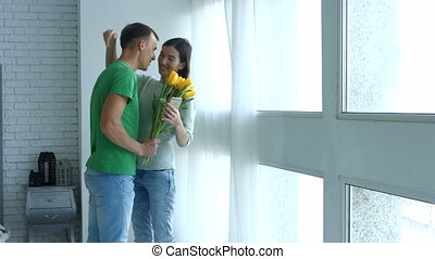 Loving man surprising his girlfriend with flowers
