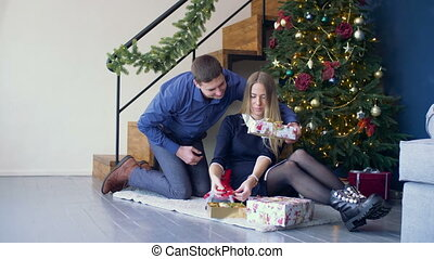 Loving man surprising his woman with christmas gift