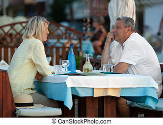 Loving mature couple having dinner in outdoor cafe