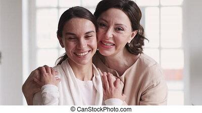 Loving mature mother hugging young daughter enjoying tenderness, portrait
