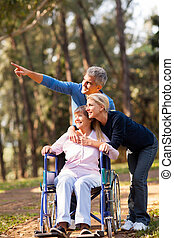 loving mid age couple taking senior mother for a walk