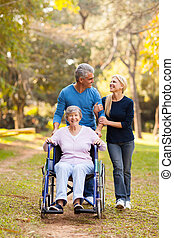 middle aged couple taking disabled mother for a walk