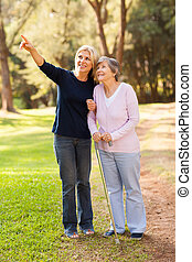 loving middle aged daughter taking senior mother for a walk