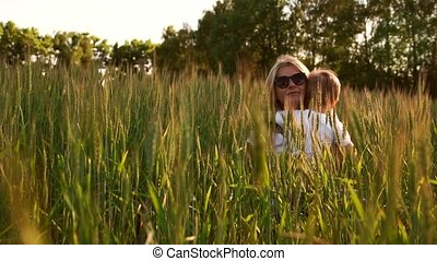Loving mom and son hugging and playing with a soccer ball in a field with spikelets in beautiful sunset light in white t-shirts