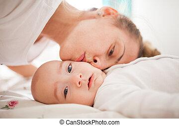 Loving mom kissing baby