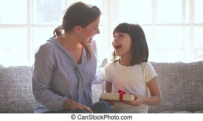 Loving mom make surprise to cute child daughter presenting gift