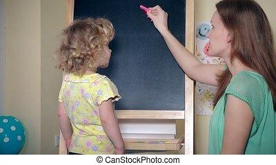 Loving mom teaching her child teaching alphabet letters on...