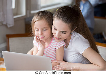Loving mom watching cartoons with daughter at laptop