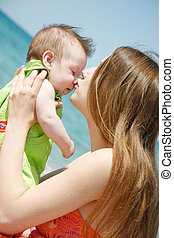 loving mother and baby on sea background