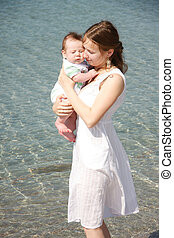 loving mother and baby on water background