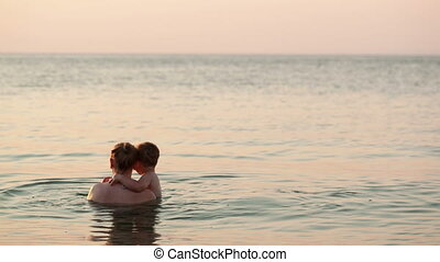Loving mother and her child bathing in the sea
