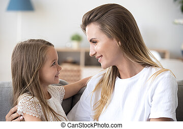 Loving mother and little daughter embracing looking in eyes