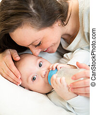 Loving mother at home feeding baby with a milk bottle