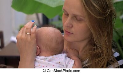 Loving mother caressing baby - Thoughtful mother stroking...