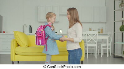 Loving mother cheering up schoolgirl at home
