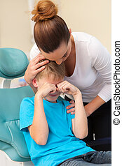 mother comforting her crying son in dentist office