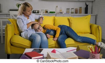 Loving mother consoling her upset daughter on sofa -...