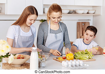 Loving mother cooking dinner with her children
