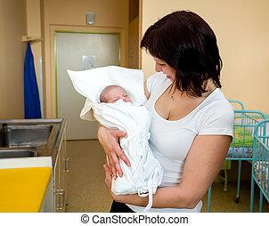 Loving mother embracing her newborn baby