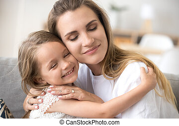 Loving mother embracing little smiling daughter showing love