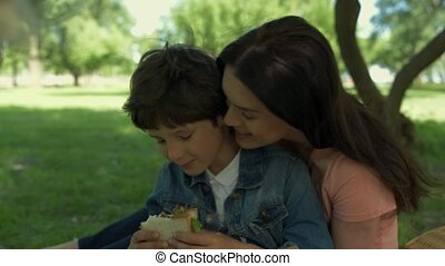Loving mother enjoying a picnic with her little son - My...