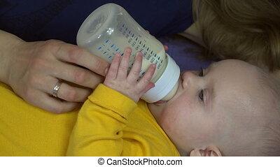 Loving mother feed newborn girl with milk powder bottle. 4K
