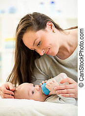 loving mother feeding her baby with a milk bottle