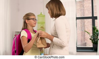 loving mother giving school lunch to daughter - education,...