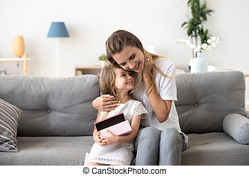 Loving mother hugging little daughter sitting together on sofa