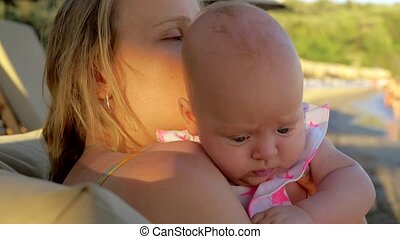 Loving mother kissing baby daughter outdoor