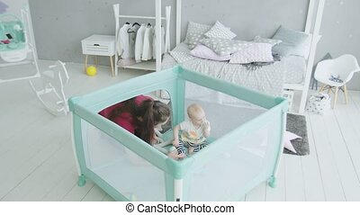 Loving mother playing with infant girl in playpen