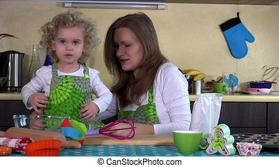 Loving mother put toddler daughter girl apron in kitchen