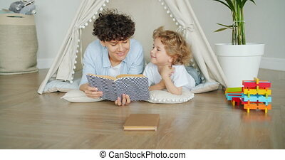 Loving mother reading book to cute child lying on floor in...