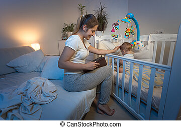 Loving mother sitting at baby's bed and reading fairy tale...