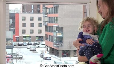 Loving mother swing naughty daughter girl on hands near...