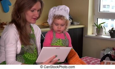 loving mother teaching daughter to cook. Family girls looking at tablet computer