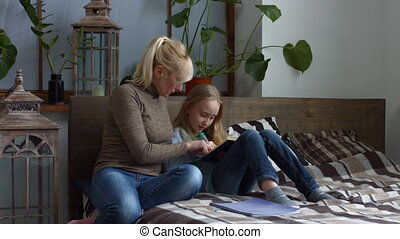 Loving mother teaching her child to read at home