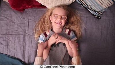 Loving mother tickling her little girl on the bed