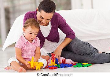 loving mother watching daughter playing