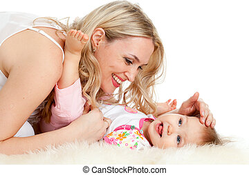 Loving mother with her baby;  child is lying on sheepskin